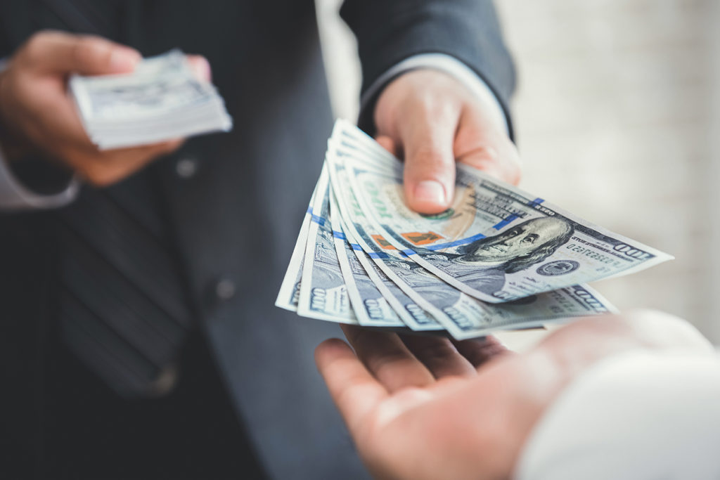 handing 100 dollar bills to customer