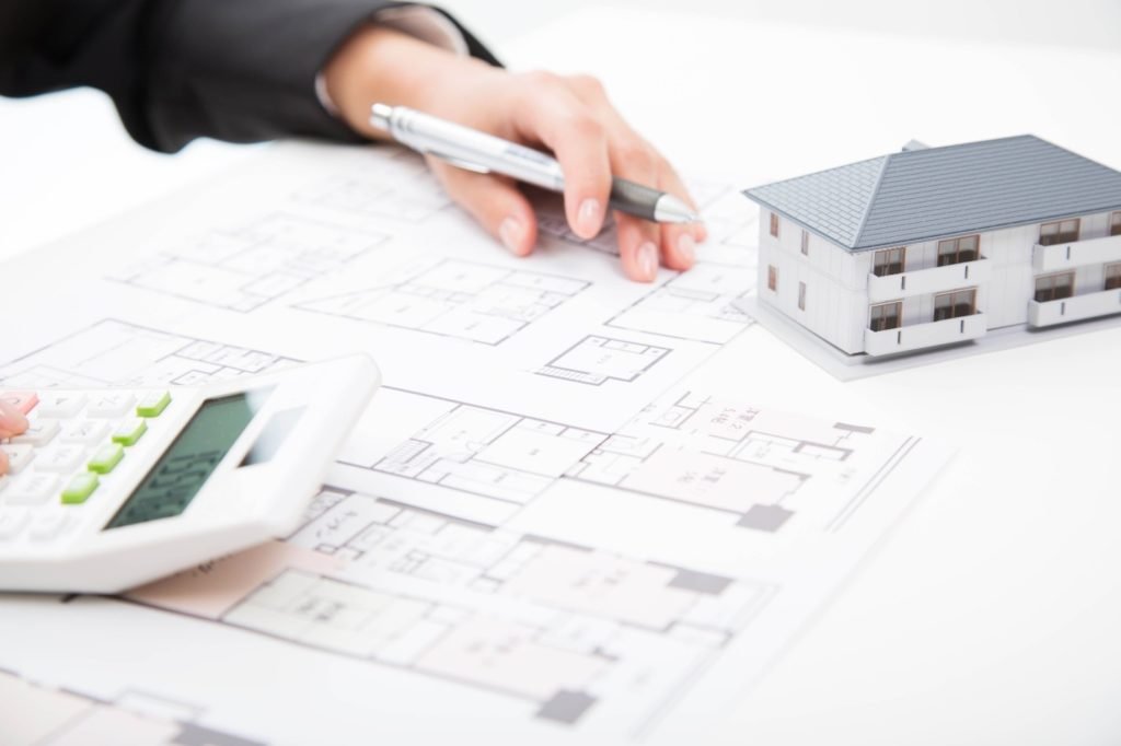 Person reviewing drawing plans for a condominium complex with a pen and calculator in hand